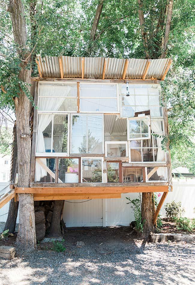 Também no estilo rústico, esta casa na árvore em madeira usa janelas de vidro para fazer uma parede livre para a iluminação do sol