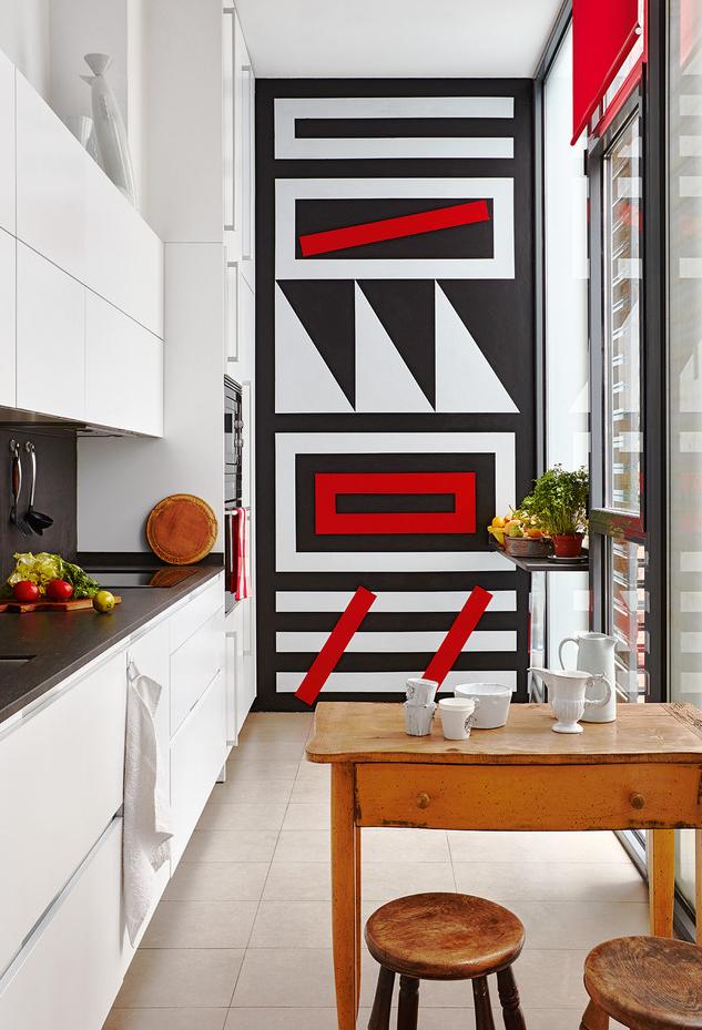 Composição na parede em preto e vermelho para chamar a atenção e trazer mais cor para esta cozinha pequena branca