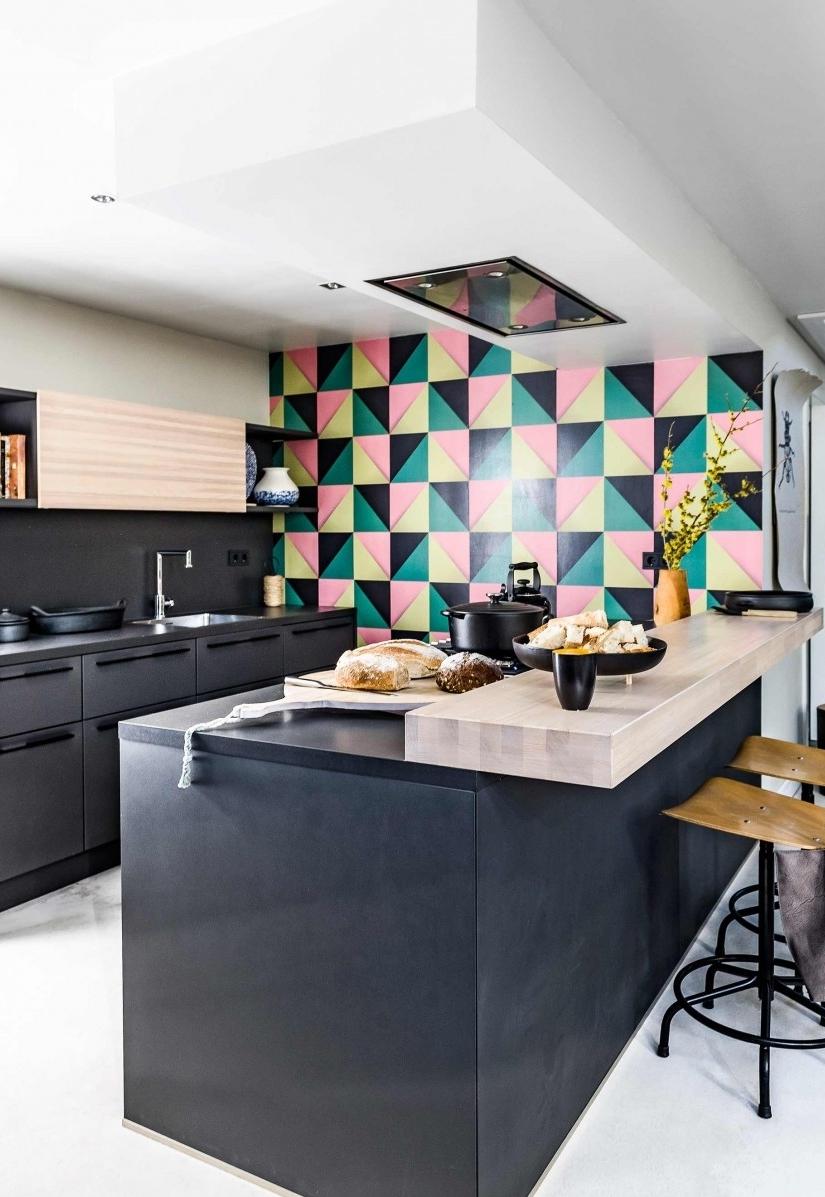 Outra ideia para dar um toque de cor é a composição na parede: esta cozinha ganha uma parede com padrão tricolor
