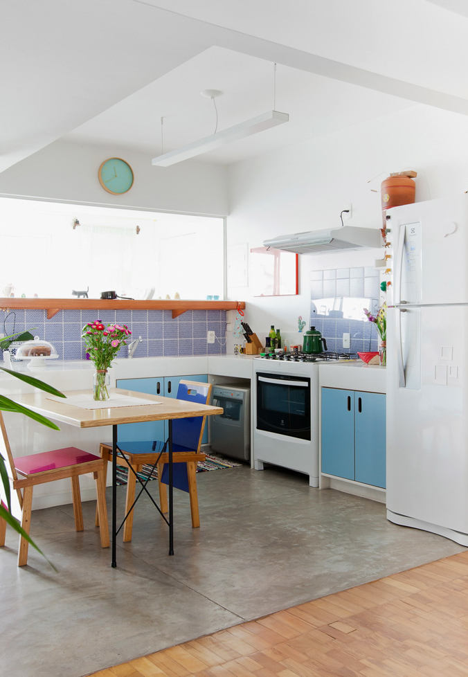 Tons de azul na parede, na bancada e cadeira desta cozinha simples e muito bem iluminada