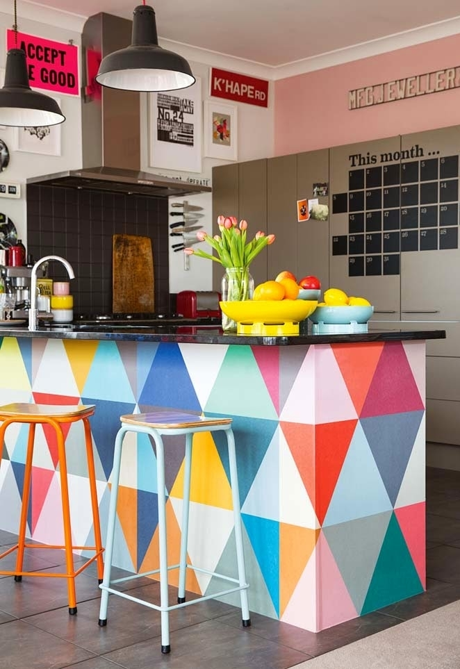 Uma cozinha cheia de referências e cores: destaque aqui para a bancada em alvenaria, pintada com um padrão triangular com tinta colorida – um projeto criativo e fácil para fazer em casa!