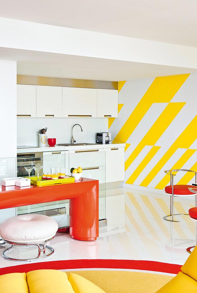 Composição em vermelho, amarelo e branco para esta cozinha integrada à sala de estar