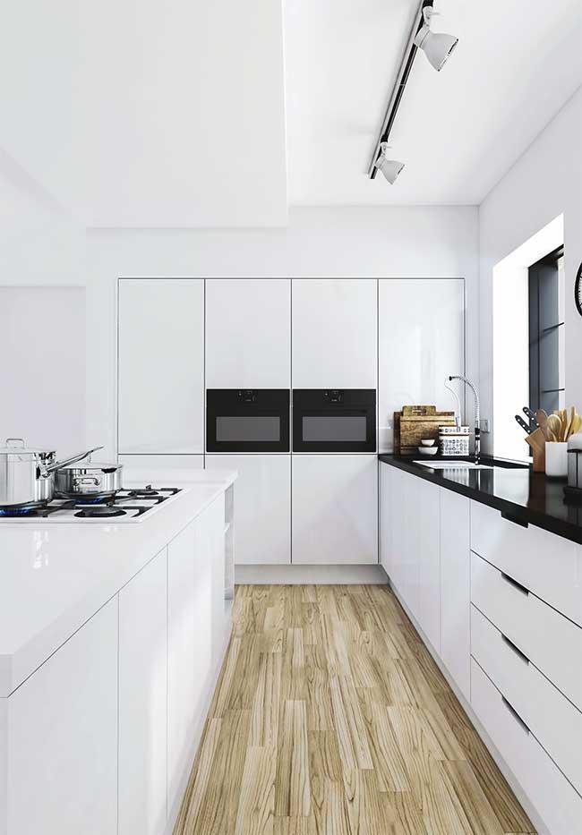 Ilha branca, combinando com o restante da cozinha, leva cooktop e armários espaçosos