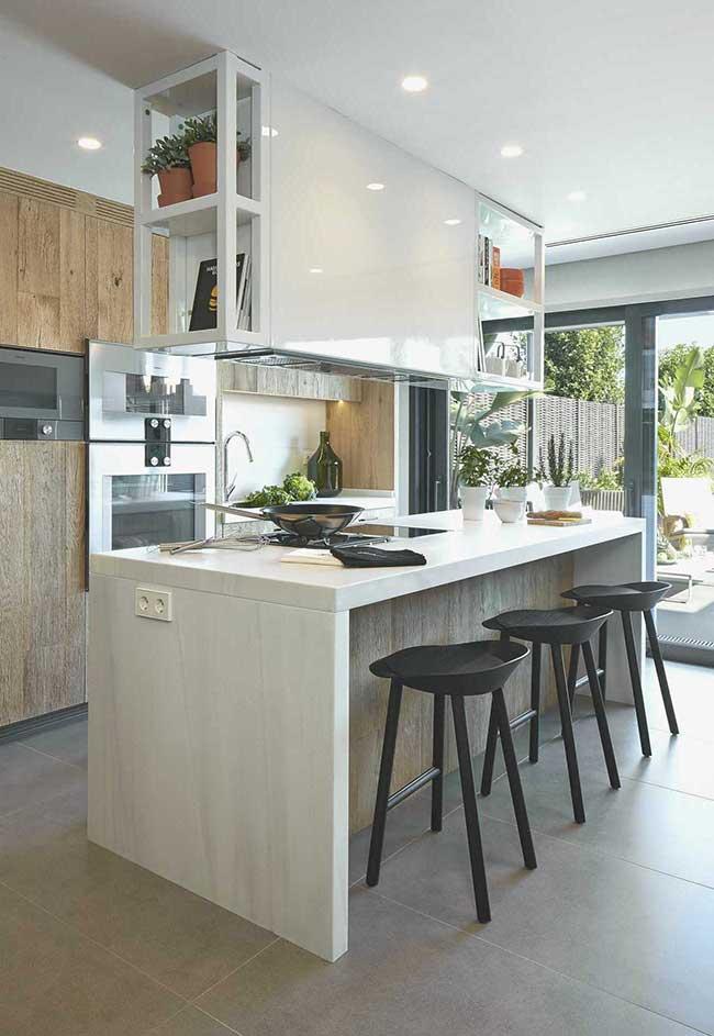 Banquetas pretas destacam o tom claro da ilha dessa cozinha com ilha
