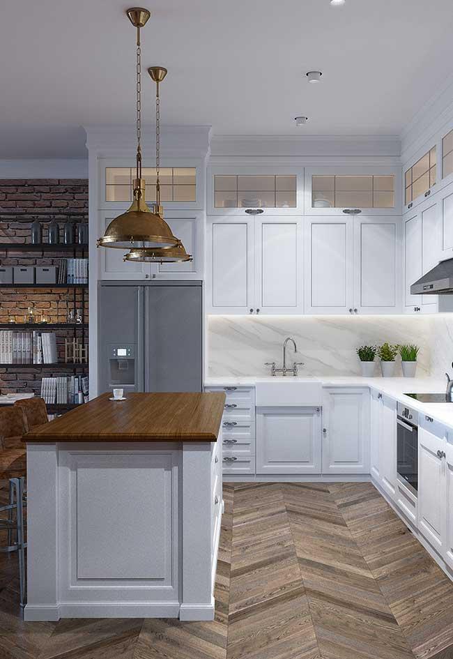 A ilha dessa cozinha é o local ideal para servir as refeições; as luminárias suspensas deixam o momento ainda mais prazeroso
