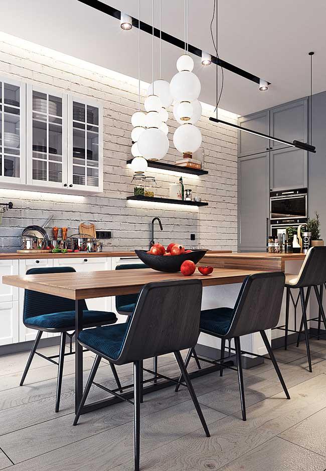 Cozinha com ilha que une estilos optou por uma ilha integrada à mesa de jantar