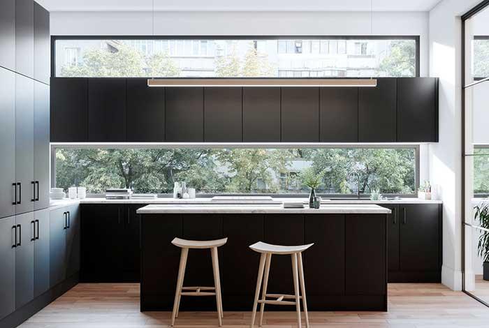 Cozinha preta com ilha central, a pedra clara sobre a ilha a destaca no ambiente