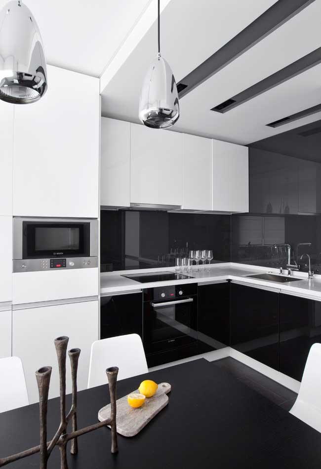 Além do fosco, o preto também aparece muito em projetos de cozinhas modernas em um acabamento esmaltado em armários e painéis