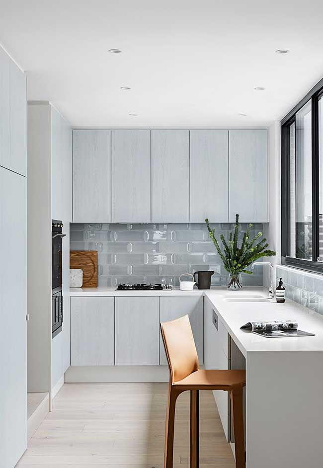A concentração de armários suspensos em uma parede só faz com que o ambiente se torne mais aberto e agradável, com boa circulação do ar e da luz natural