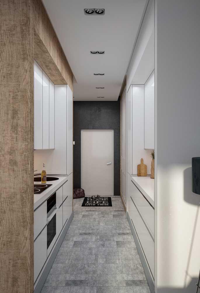 Em ambientes tipo corredor, vale pensar em embutir os armários planejados nas paredes laterais, criando uma circulação central no ambiente