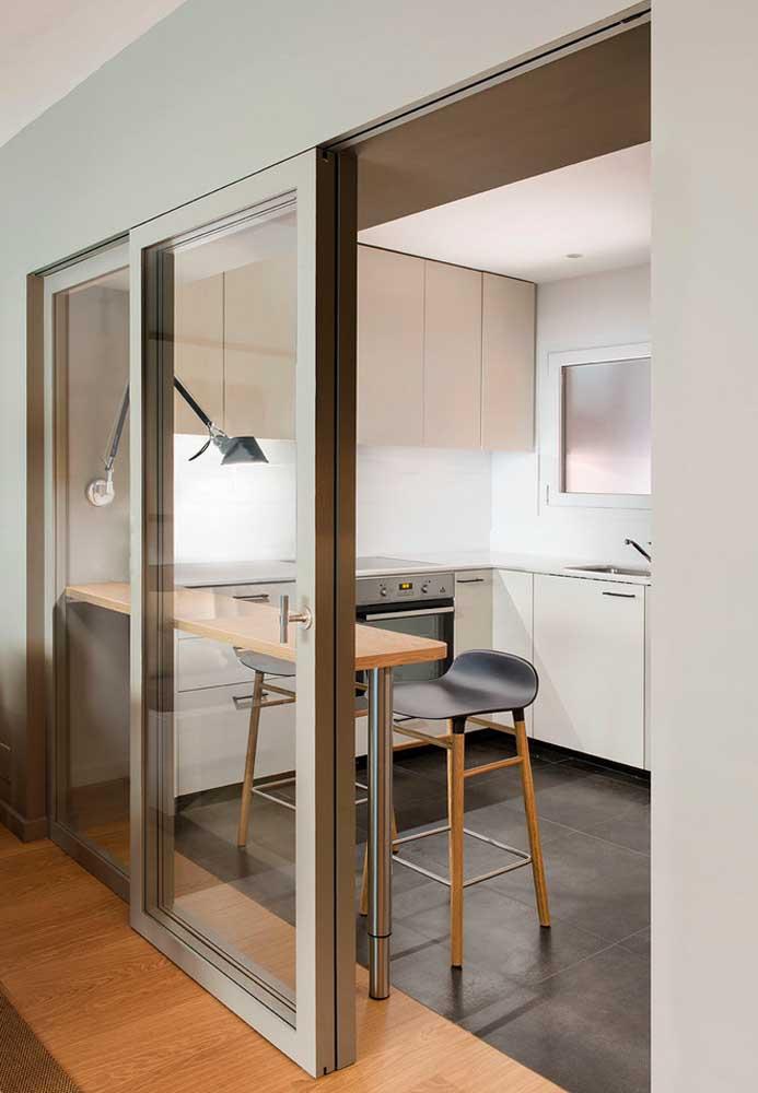 Uma boa ideia para dividir ambientes sem isolá-los e deixar a luz passar é utilizar paredes ou portas de vidro, como nesta cozinha pequena