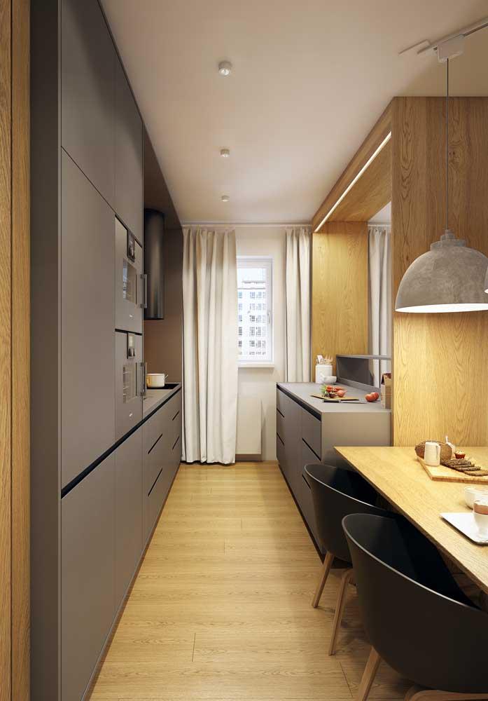 Outra ideia de ambiente conjugado que usa a cozinha pequena como uma separação entre os espaços