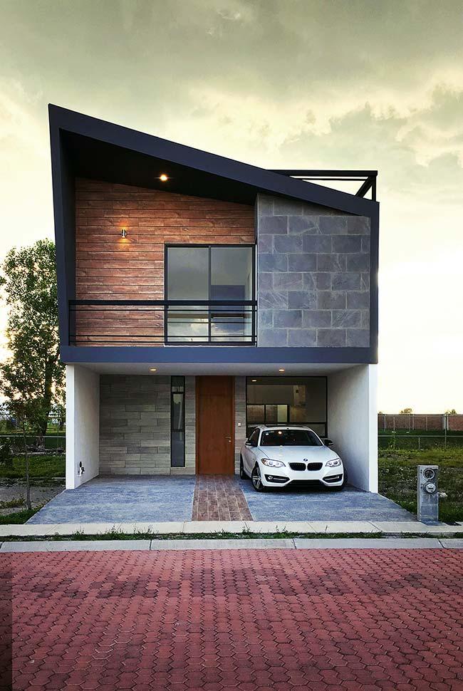 Sobrado moderno com fachada que mescla madeira, pedras e metal