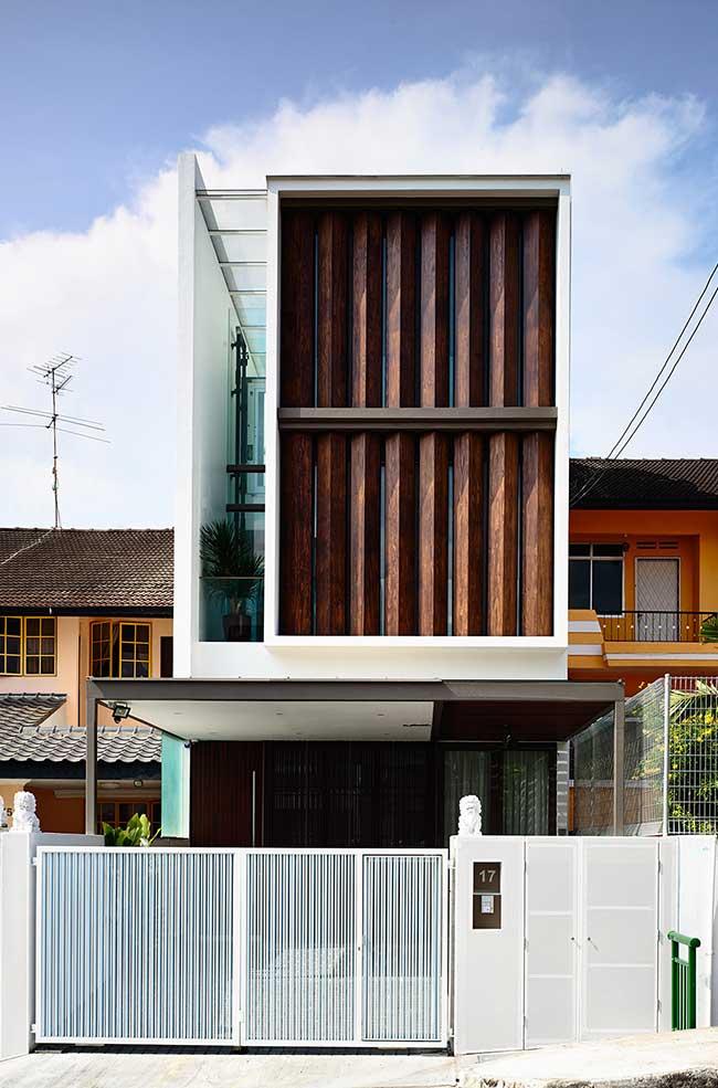 Troncos rústicos de madeira formam a fachada desse sobrado