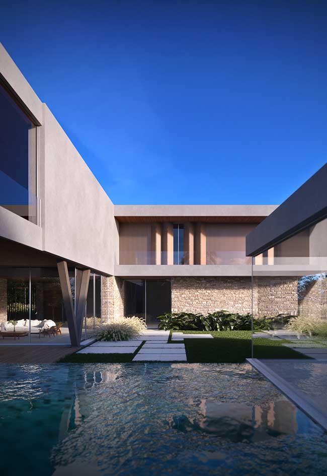 Fachada de pedra valorizada pela piscina e o piso gramado
