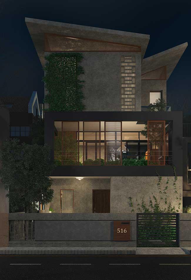 Fachada de casa rústica toda de concreto aparente ganhou um 'quê' a mais com o jardim vertical