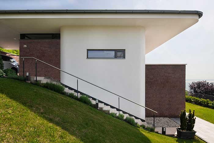 Casa de estruturas arredondadas destaca em sua fachada um gramado muito bem cuidado