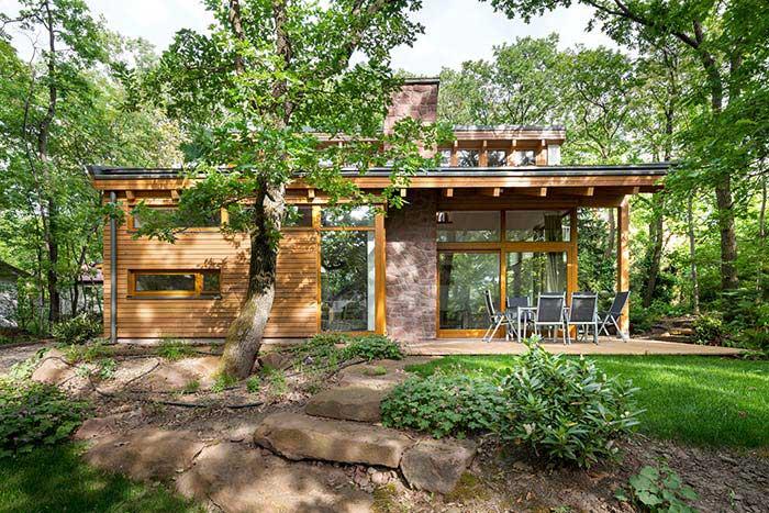 Uma fachada não tem como ser mais aconchegante do que quando prioriza o uso de materiais como madeira e pedras, especialmente se o local é cercado pela natureza