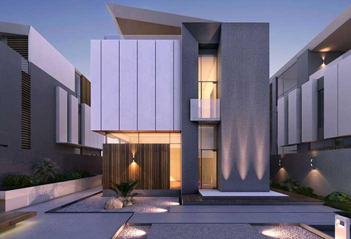 Jardim de pedras, deck de madeira e iluminação indireta na fachada da casa