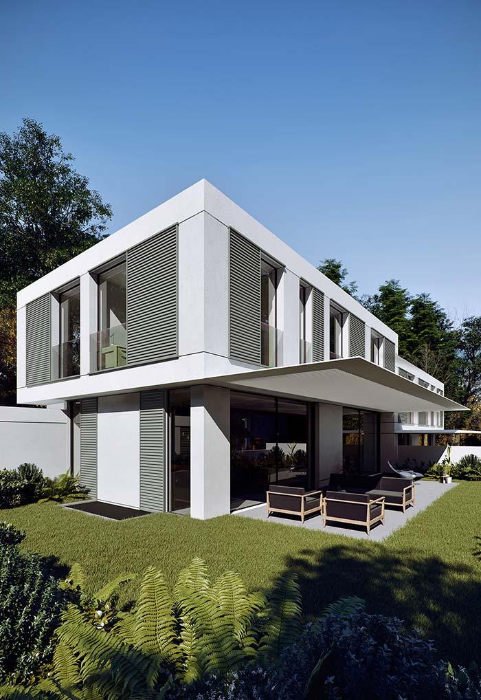 A casa toda branca se destaca sobre o gramado verdinho