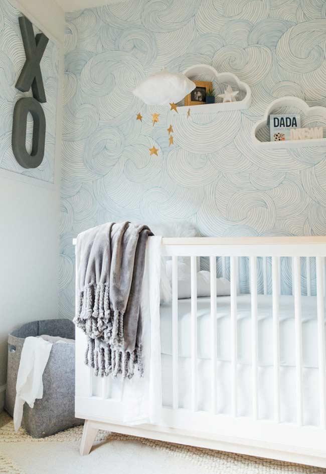 Papel de parede com ondas estilizadas fazem um céu azul clarinho perfeito para o móbile de estrelas e os nichos em forma de nuvens na parede