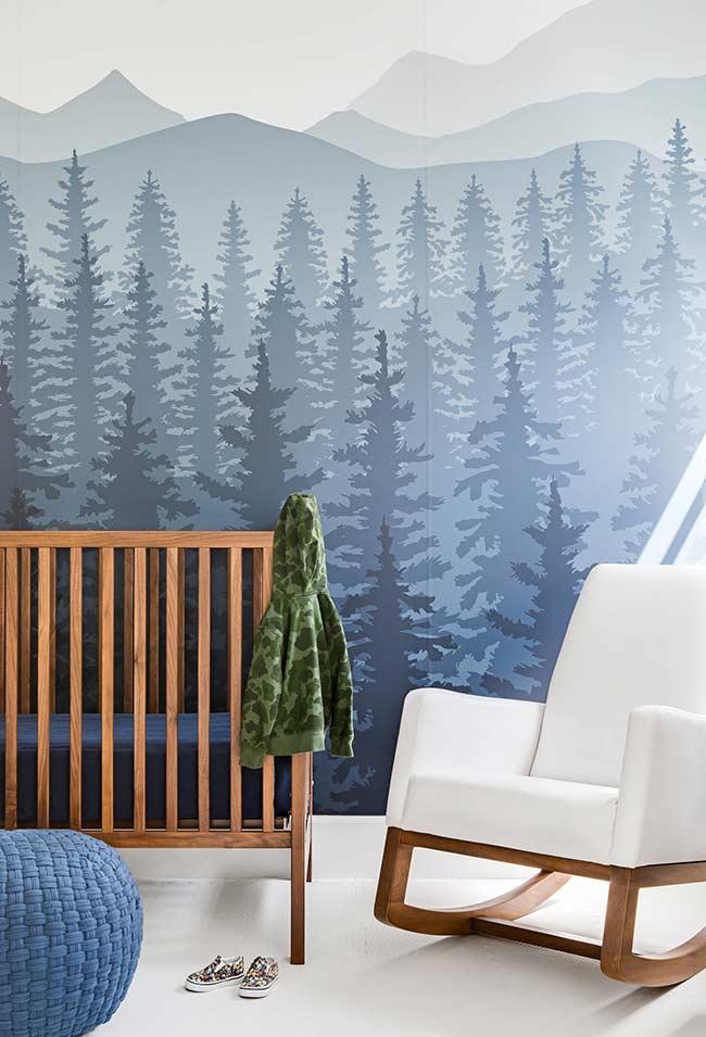papel de parede azul com uma vista incrível das montanhas e dos pinheiros neste quarto de bebê