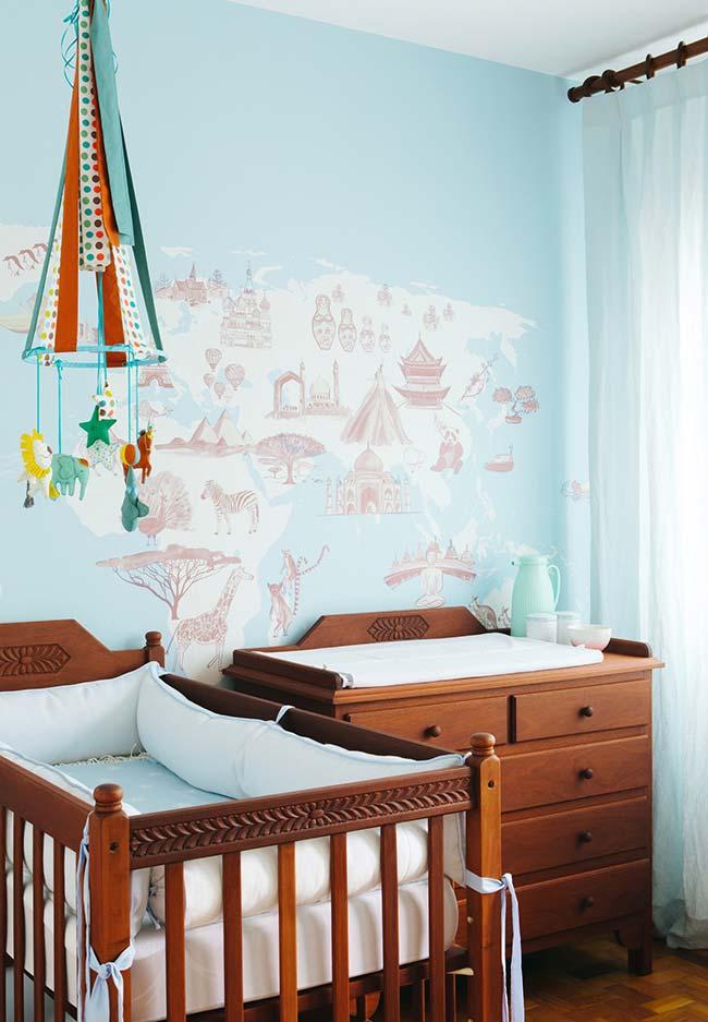 Um quarto de bebê masculino em azul, madeira mogno e um papel de parede cheio de descobertas para fazer pelo mundo