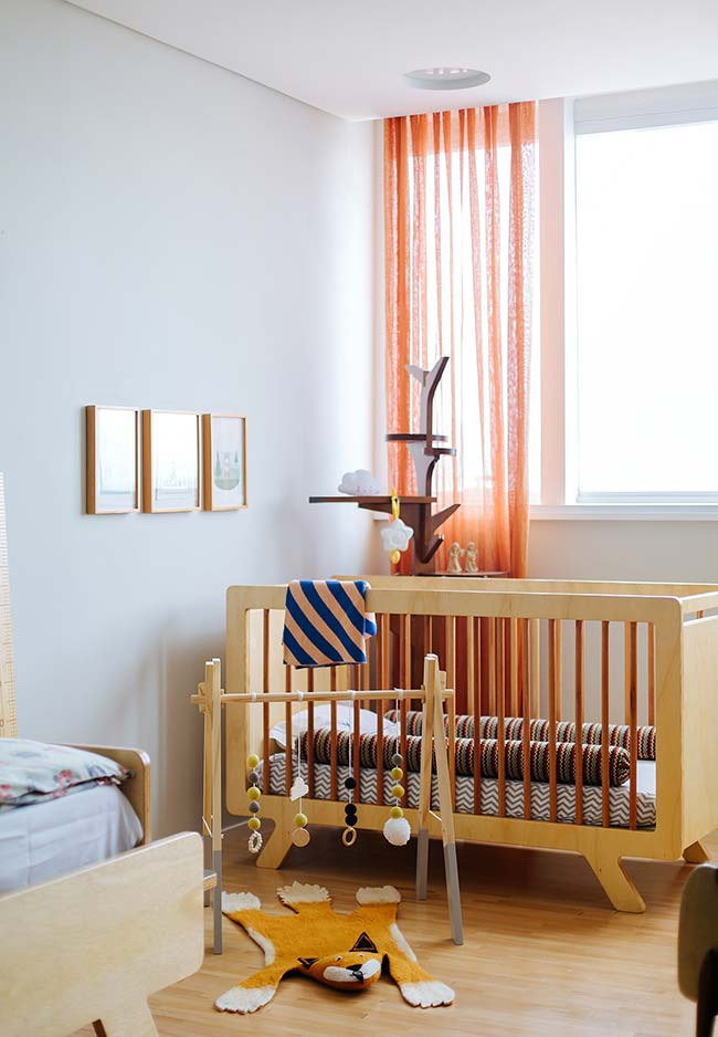 Madeira clarinha nos móveis e brinquedos deste quarto de bebê