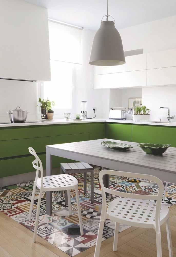 Uma faixa verde nesta cozinha branca: o acabamento dos armários, as plantinhas e as louças verdes chamam nossa atenção e formam a unidade da decoração