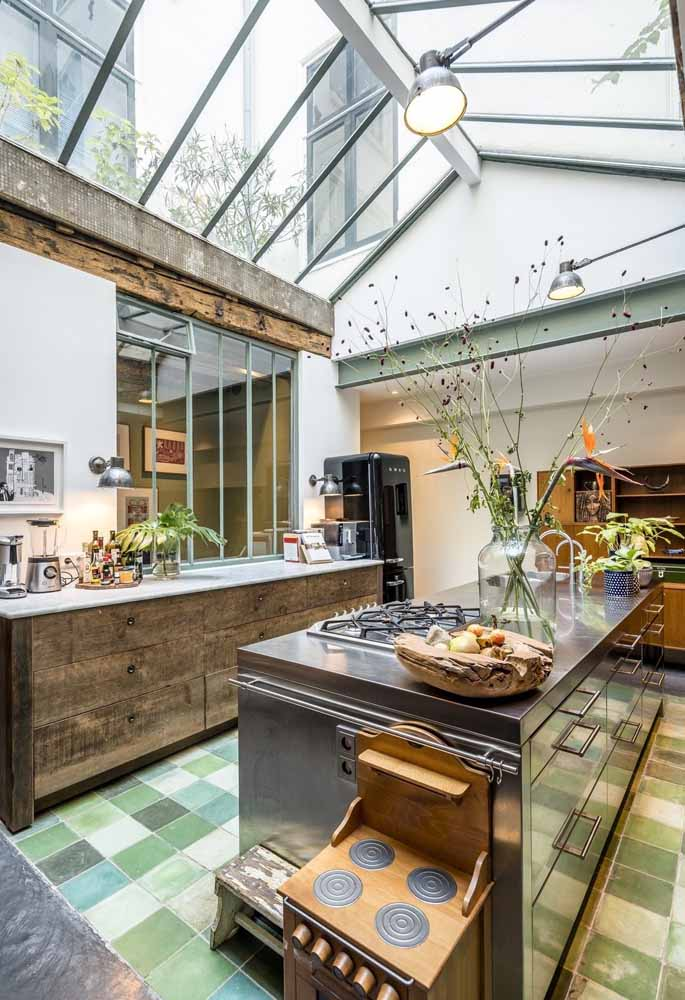 Um mix moderno e rústico nesta cozinha com um piso mosaico com diversos tons de verde para brincar e compor