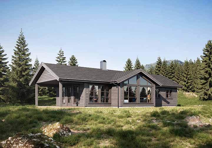 Uma casa de madeira cinza em contraste com o verde da natureza ao redor