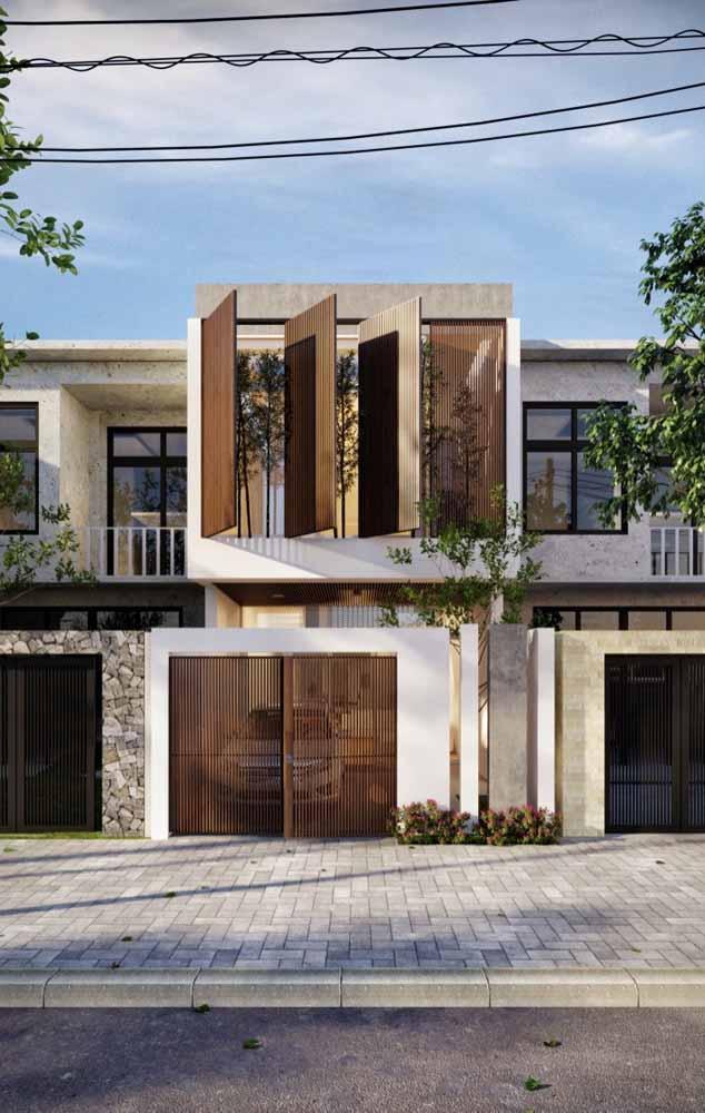 Podia ser só mais um sobrado com garagem, mas esse aqui ganha um destaque extra com as enormes janelas de madeira