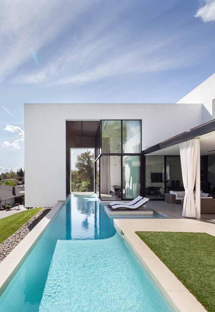 Casa moderna de alvenaria e vidro; só ela já seria suficiente para chamar a atenção, mas é a piscina que percorre toda a extensão da casa que se destaca