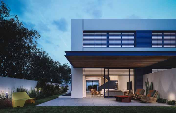 Uma casa bonita, sem dúvida, mas o que chama a atenção mesmo é o singelo banco amarelo no jardim