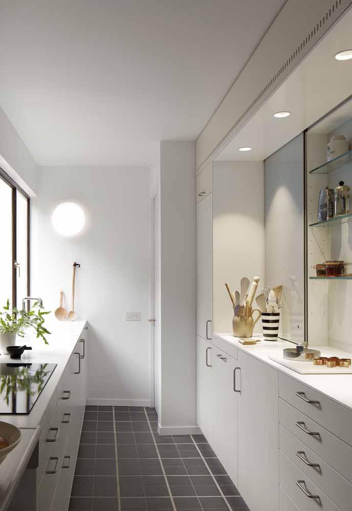 Cozinha branca corredor: para apartamento, com vantagem de ter armários em ambos lados, aparador e bastante claridade misturando a luz natural com artificial