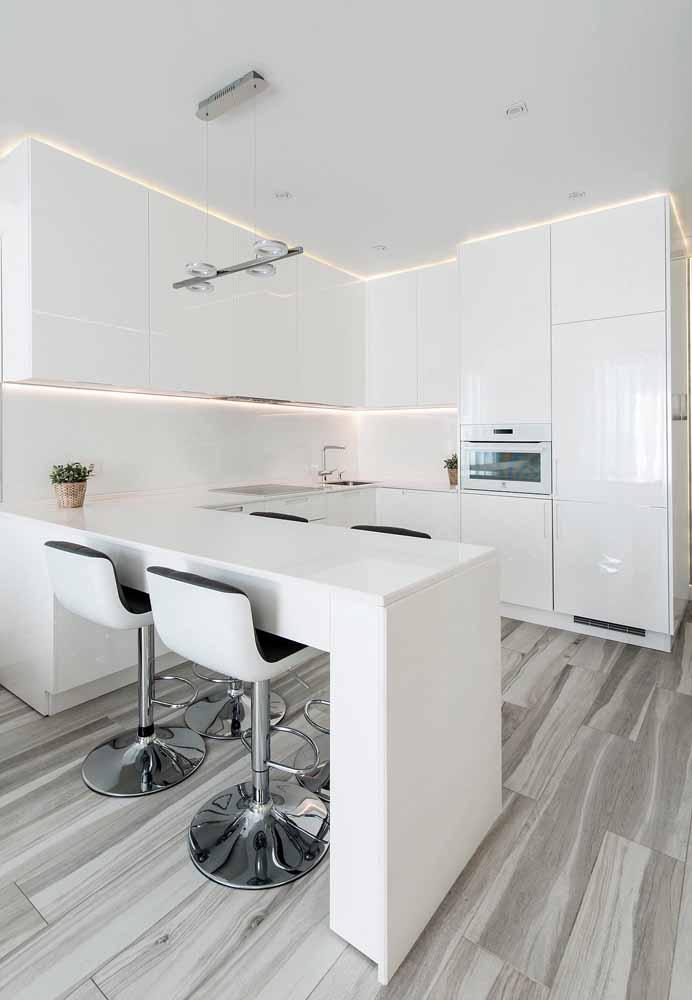 Cozinha branca pequena ao estilo americano, bancada com quatro cadeiras com detalhe de pés em inox para realçar o piso imitando madeira