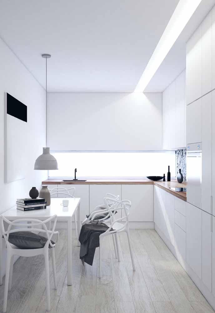 Cozinha branca em L: Armários até o teto, pendente sobre a mesa transmitindo sofisticação com luz de Led