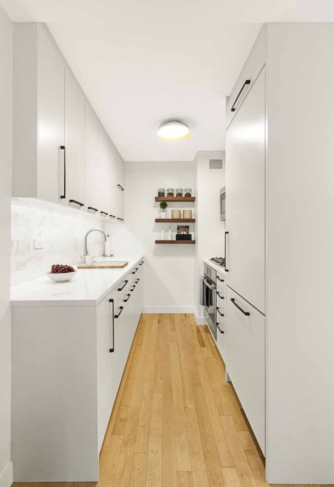 Cozinha branca corredor: Cozinha com armários logos até o teto e puxadores em detalhes pretos. e prateleiras ao fundo com temperos à mostra harmonizando com a decoração