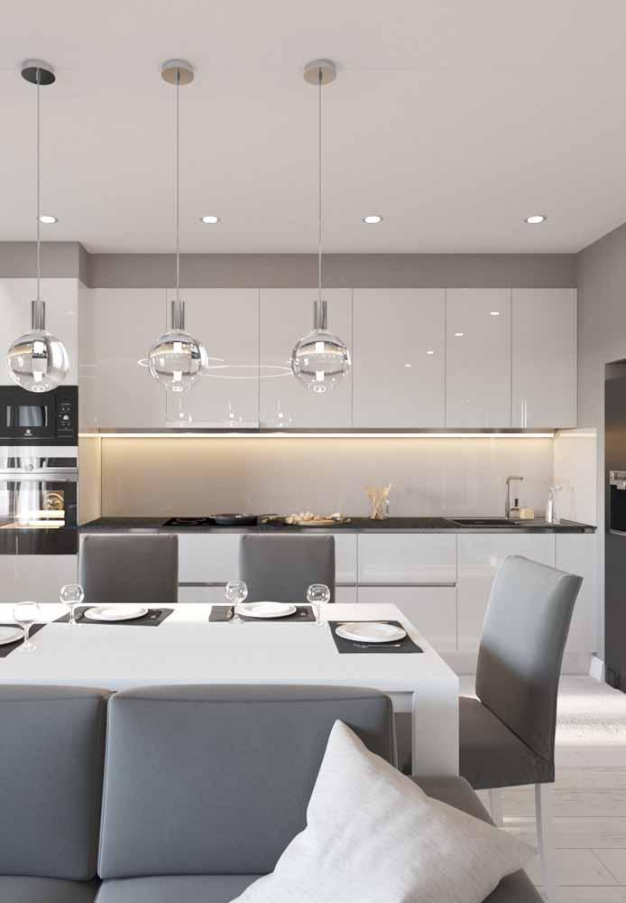 Cozinha branca e cinza moderna integrada com a sala para interação quando se recebe visitas