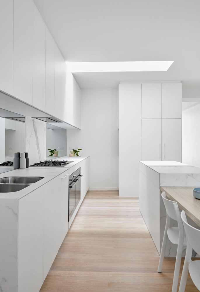 Cozinha branca gourmet com mesa acoplada ao balcão: Muito comum para melhor transição na cozinha