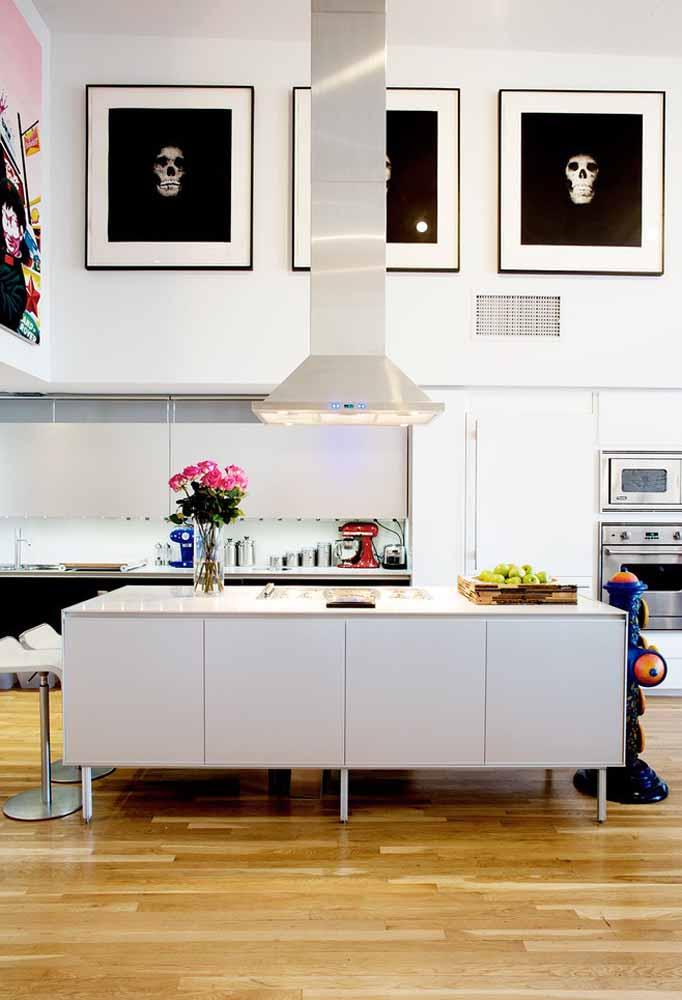 Cozinha branca em ilha ou península é referência para uma cozinha gourmet. Quadros grandes dão destaque e arrasam no visual