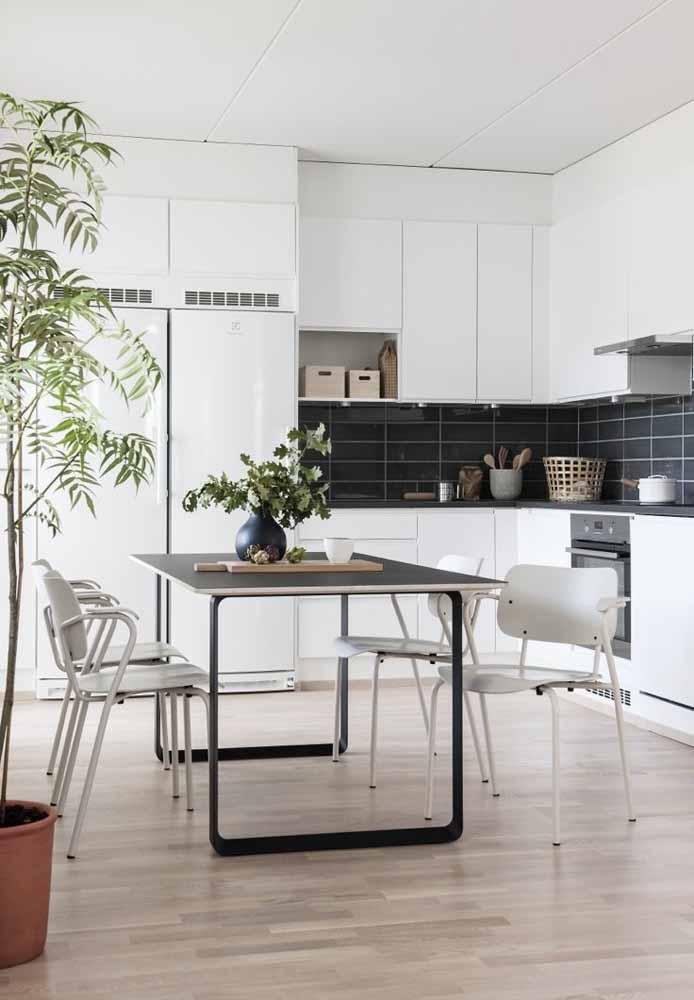 Cozinha branca com mesa preta e plantas para leveza do ambiente