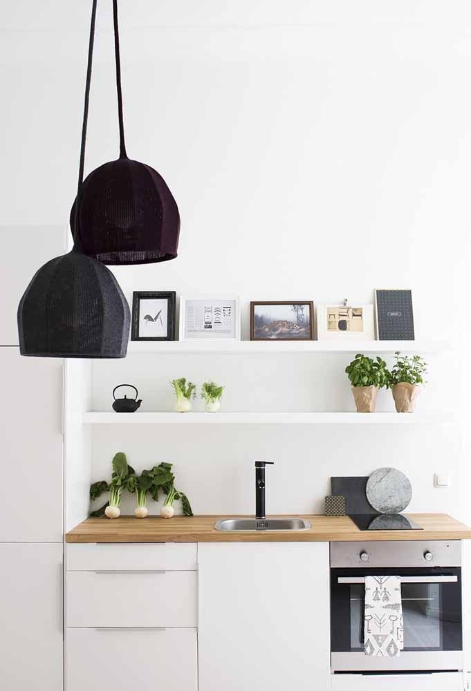 Legumes à mostra em cozinha branca com retratos e plantas