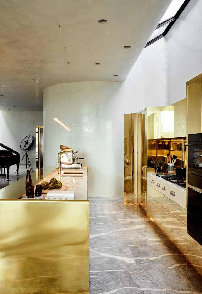 Cozinha de luxo que aposta na combinação de um ambiente industrial com mobiliário dourado