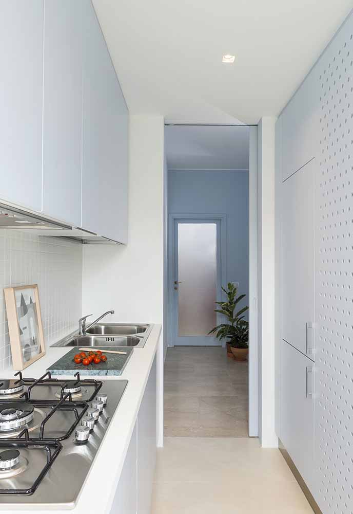 Nas cozinhas estreitas, a dica é sempre manter a pia, fogão e geladeira na mesma linha, como nesta imagem, para facilitar a circulação