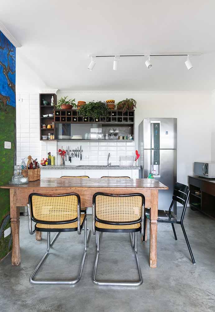 Cozinha simples e diversa resolvida em uma parede só: um balcão grande de pedra com nicho suspenso de madeira