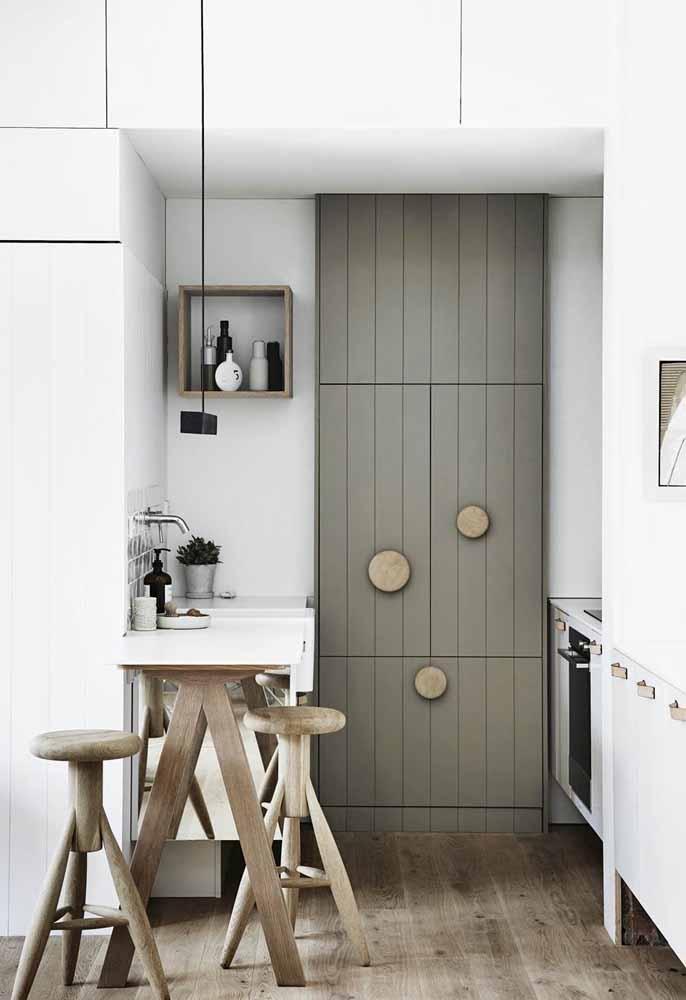 Um armário com design diferente ganhando destaque nesta cozinha simples e pequena