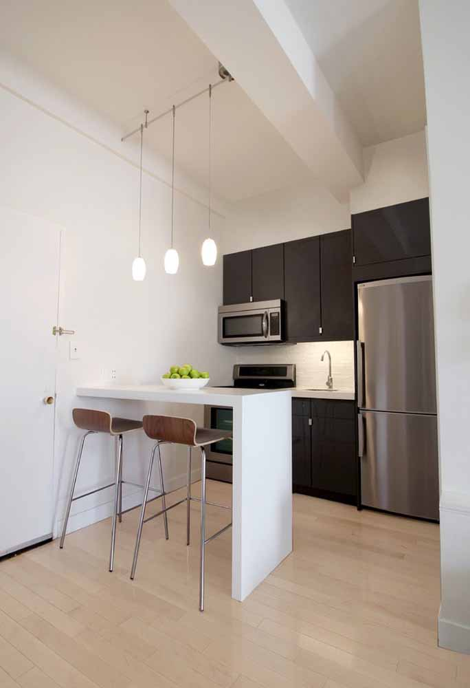 Decoração de cozinha simples com bancada: aqui ela ganha dupla função, tanto de dividir o espaço do ambiente quanto de servir de apoio para as refeições