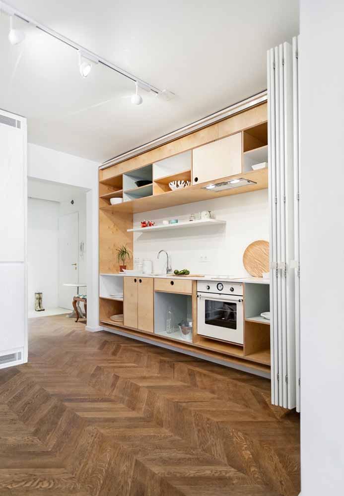 Funcionalidade para o espaço: de uma cozinha simples e muito bem projetada, à uma sala extra para receber os convidados com uma porta de distância