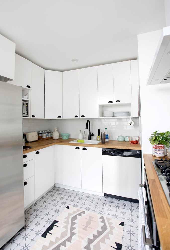 O preto como opção de acabamento para puxadores num contraste com os armários brancos para mais estilo nesta cozinha